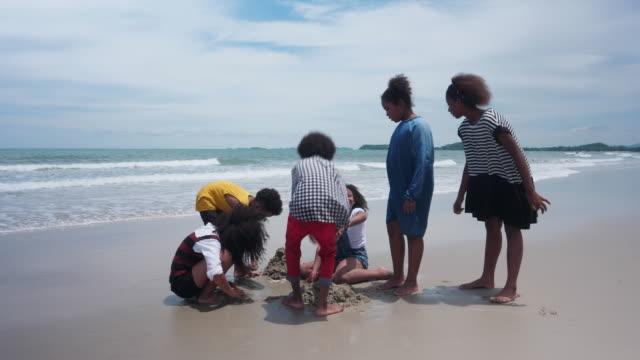 gruppe afrikanischer kinder, die am strand im sand spielen - 8 9 jahre stock-videos und b-roll-filmmaterial
