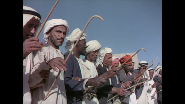 group of arab men in traditional clothes with ceremonial daggers in their belts gathered in a ceremonial dance chanting singing drumming - 1965 stock videos & royalty-free footage