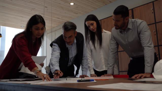 gruppe von architekten in einem coworking büro, die an entwürfen für ein projekt arbeiten - anweisungen geben stock-videos und b-roll-filmmaterial