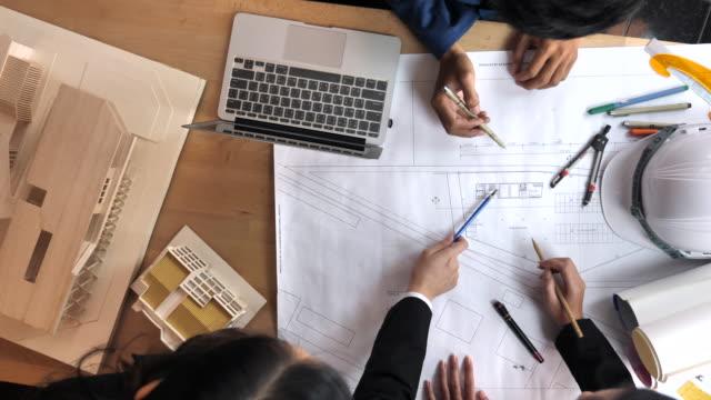 Grupp av arkitekter frma och prata tekniska ritningar