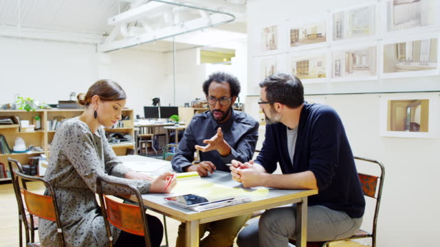 MS group of architects discussing project at small conference table in office