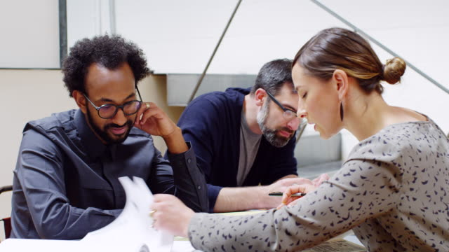 MS group of architects examining project plans at conference table in office