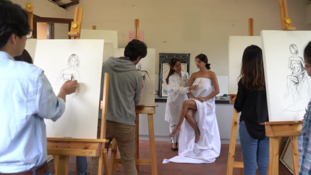 group of art students drawing a model on canvas while teacher points out different aspects to detail - art class stock videos & royalty-free footage