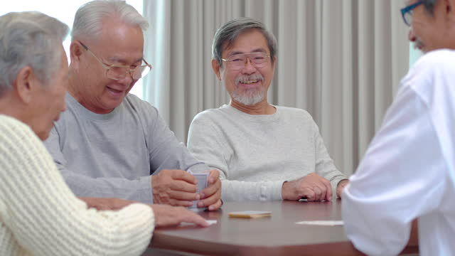 group of asian active seniors age 60-70 yearold with group of happy old friends playing cards while talking spending a great time all together at nursing home.social seniors - chinese ethnicity stock videos & royalty-free footage