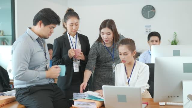 stockvideo's en b-roll-footage met groep aziatische zakenmensen met casual pak brainstormen of praten terwijl een pauze voor informele vergadering in het moderne kantoor, business group concept. - mannelijke gelijkenis