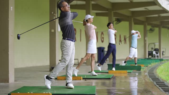 group of asian chinese golfers playing golf at driving range golf course - country club stock videos & royalty-free footage