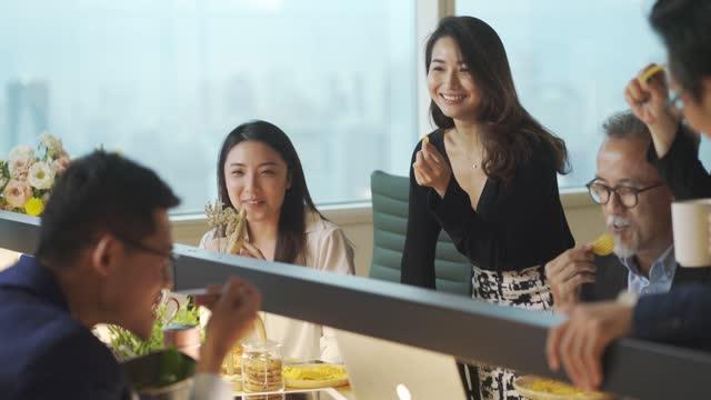 仕事の遅れで休憩を取り、ワークステーションオフィスのオフィスでのボンディングでスナックを取っているアジアの中国のホワイトカラー労働者のグループ - 分かち合い点の映像素材/bロール
