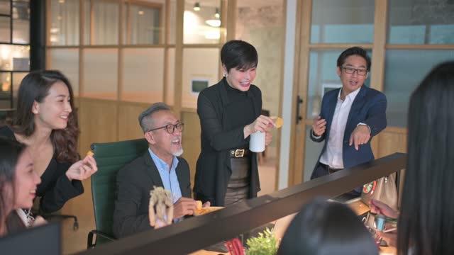 仕事の遅れで休憩を取り、ワークステーションオフィスのオフィスでのボンディングでスナックを取っているアジアの中国のホワイトカラー労働者のグループ - 談笑する点の映像素材/bロール