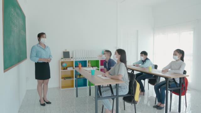 学校に戻りながら教室でcovid 19が発生するのを防ぐために衛生的なマスクを着用したアジアの小学生と教師のグループは、教育コンセプトのための新しい正常。 - 新学期点の映像素材/bロール