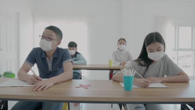 学校に戻りながら教室でcovid 19が発生するのを防ぐために衛生的なマスクを着用したアジアの小学生のグループは、教育コンセプトのための新しい正常。 - 新学期点の映像素材/bロール