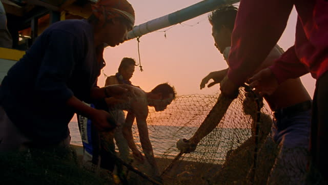 vidéos et rushes de ms group of asian fishermen pulling up net on boat / sun setting over ocean in background / java, indonesia - pêcheur