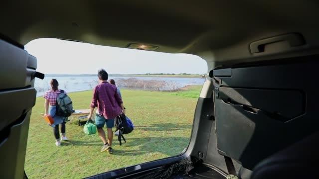 eine gruppe asiatischer freunde half, tasche und ukelele zu heben und essen aus dem auto zu holen, um in den sommerferien zum picknick zu gehen. sie sind glücklich und haben spaß am urlaub. - transportmittel stock-videos und b-roll-filmmaterial