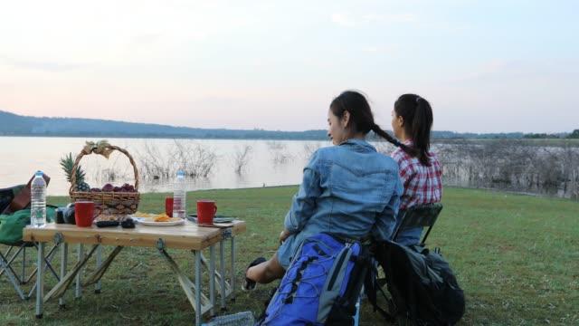 stockvideo's en b-roll-footage met een groep van aziatische vrienden spelen ukelele en tijd doorbrengen met het maken van een picknick in de zomervakantie. ze zijn blij en plezier hebben op vakantie. - koffie drank