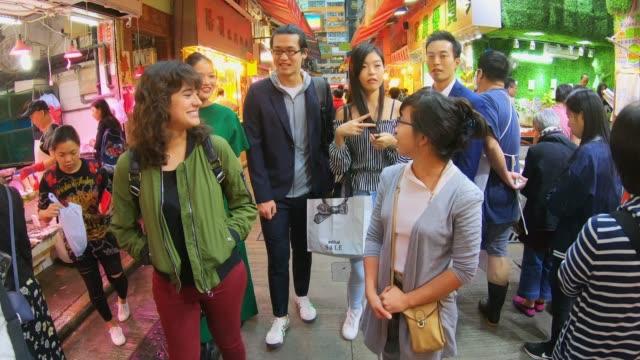 group of asian friends shopping in hong kong night market - hong kong stock videos & royalty-free footage