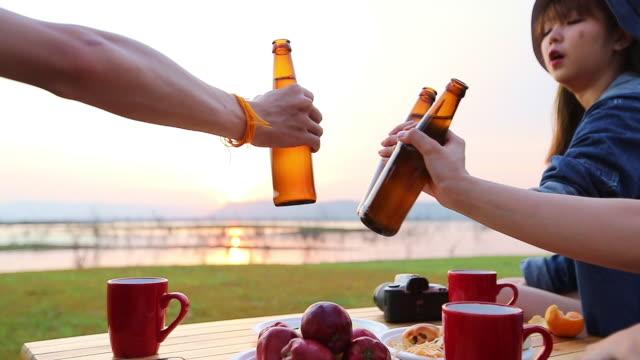 stockvideo's en b-roll-footage met een groep van aziatische vrienden toeristische drinken alcoholische bier en het spelen van gitaar samen met geluk in de zomer terwijl het hebben van camping in de buurt van het meer bij zonsondergang - koffie drank