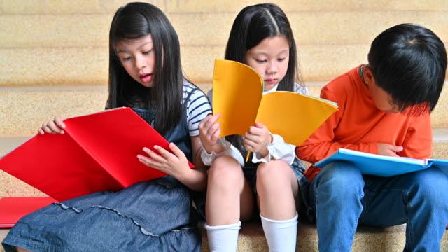vidéos et rushes de un groupe d'enfants d'asie lecture livre ensemble - élève du primaire
