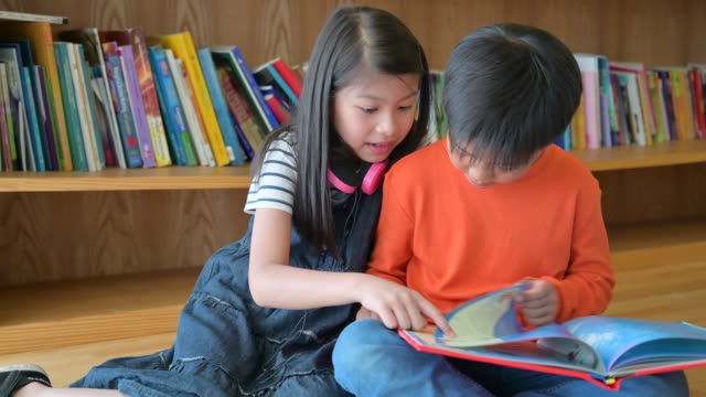 a group of asian kids reading book together - awe stock videos & royalty-free footage
