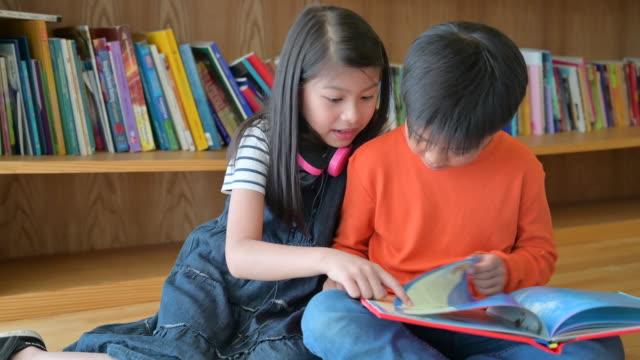 en grupp av asiatiska barn läsa bok tillsammans - vördnad bildbanksvideor och videomaterial från bakom kulisserna