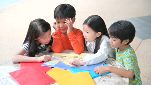 a group of asian kids reading book together - comfortable stock videos & royalty-free footage