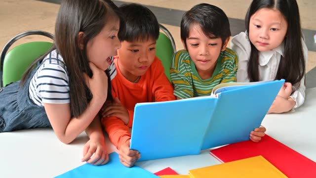 a group of asian kids reading book together - book stock videos & royalty-free footage