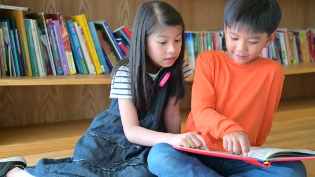 stockvideo's en b-roll-footage met een groep van aziatische kinderen lezen boek samen - prentenboek
