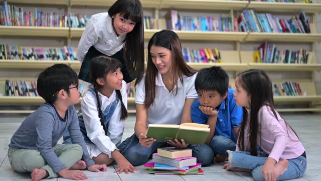 stockvideo's en b-roll-footage met een groep aziatische jonge geitjes lezingsboek samen met leraar in de bibliotheek van de school, plank van boek op achtergrond - prentenboek