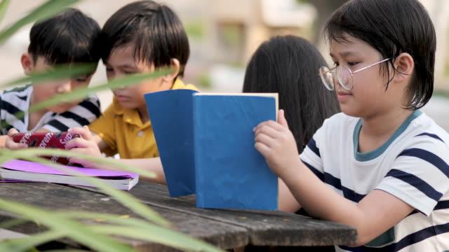 vídeos y material grabado en eventos de stock de un grupo de niños asiáticos libro de lectura. - historia