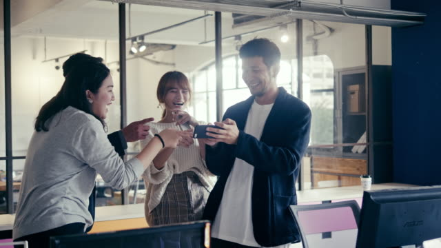vídeos de stock e filmes b-roll de group of asian millennials watching and laughing on the video in office party (slow motion) - employee engagement