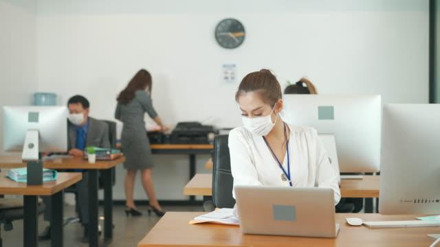 vidéos et rushes de groupe de personnes d'affaires asiatiques d'âge mixte travaillant dans le bureau avec le nouveau concept normal de mode de vie social distanciant. l'homme et la femme portent le masque protecteur et continuent de prendre leurs distances pour empêch - new age concept