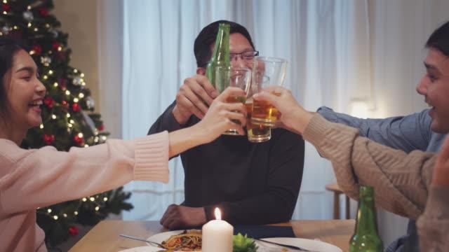 4k uhd :テーブルの周りに座って、食べて、コミュニケーションし、自宅で夜に友人との関係を楽しむアジアの人々のグループ。 - アルコール飲料点の映像素材/bロール