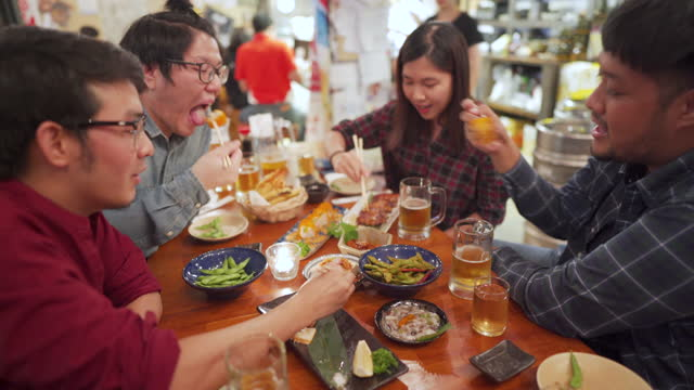 a group of asian salaryman dining and cheering with food and beer in japanese izakaya - japanese food stock videos & royalty-free footage