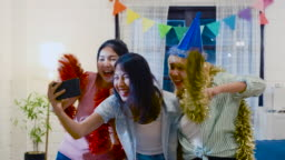 Group of asian woman friend enjoy new year party and use mobile selfie while dancing in living room at home at night.celebration holiday festive concept