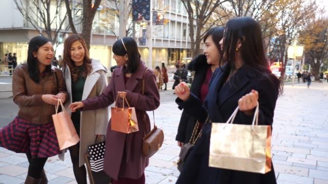 クリスマスの日に商店街を歩くアジアの女性のグループ - 談笑する点の映像素材/bロール