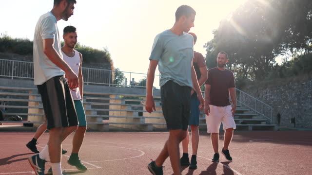 暖かい春の日に屋外のコートでバスケットボールの試合を楽しむアスリートの友人のグループ。 - スポーツ バスケットボール点の映像素材/bロール