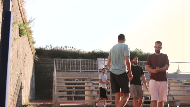 vidéos et rushes de groupe d'amis d'athlète appréciant un jeu de basket-ball sur un court extérieur pendant une chaude journée de printemps. - streetball