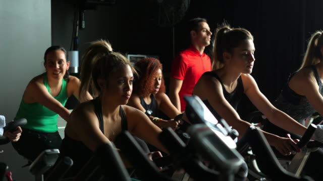 pan group of athletes riding stationary bikes during fitness class in exercise studio - fitnesskurs stock-videos und b-roll-filmmaterial