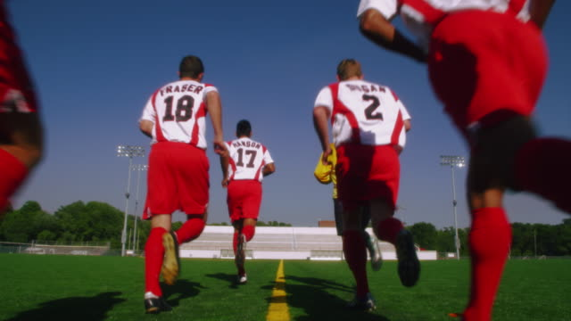 slo mo. group of athletic soccer players in their jerseys jog across a soccer field - football pitch stock videos and b-roll footage