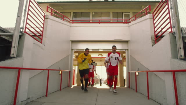 SLO MO. Group of athletic soccer players in their jerseys jog down the entrance ramp of a stadium to the field for a game while cheering and clapping at the camera