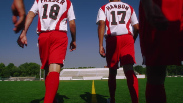 vídeos y material grabado en eventos de stock de slo mo. group of athletic soccer players in their jerseys walk across a soccer field - campo de fútbol