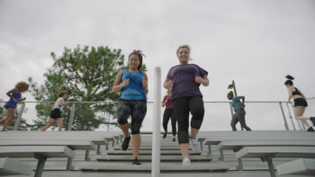 group of athletic women run down the staircase of a set of bleachers for exercise - sweat stock videos & royalty-free footage