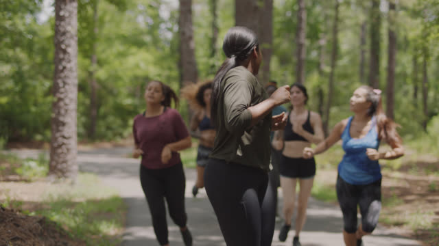 group of athletic women running on a path in the forest together slow down to allow others to catch up - smart watch stock videos & royalty-free footage