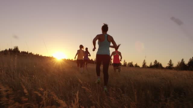 Gruppe von attraktiven Läuferinnen bei Sonnenuntergang im freien laufen