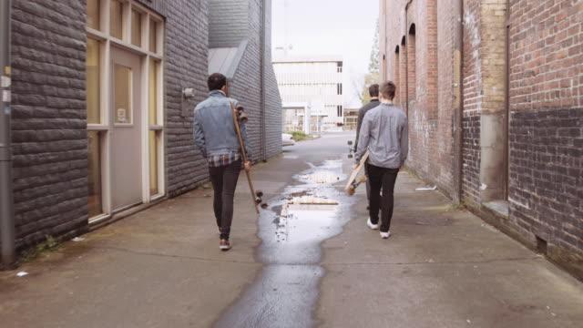 vídeos y material grabado en eventos de stock de grupo de hombres jóvenes atractivos en el callejón - surf en longobard