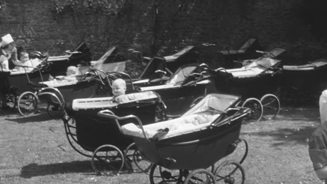 1950 pan group of baby carriages on outdoor lawn and two nannies sitting in chairs holding nursing infants at group home institution / united kingdom - orphan stock videos & royalty-free footage