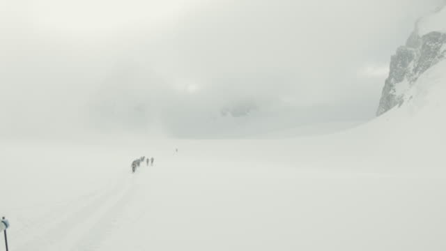 Group of backcountry skiers skiing in bad weather in Swiss Alps