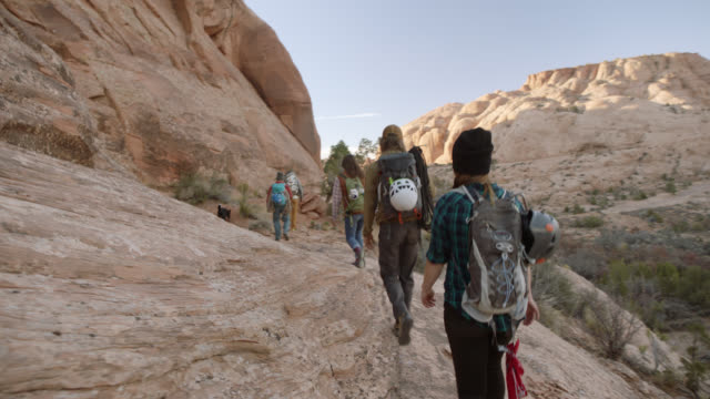group of backpacking friends walk in single file down rocky moab trail through entrajo canyon. - wilderness stock videos & royalty-free footage