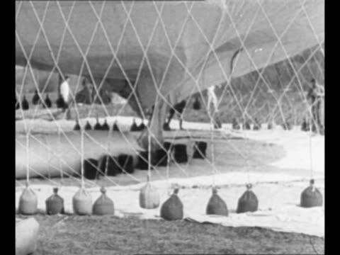 vídeos y material grabado en eventos de stock de group of balloons on ground await signal to start in 1929 gordon bennett cup an annual balloon race / man tethers balloon to ground using sandbags... - danish flag