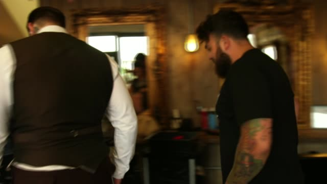 group of barbers work with mental health charities to help men suffering from depression; int paul entering barber shop and shaking hands with tom... - cut video transition stock videos & royalty-free footage