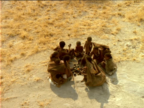 Group of Basarwa tribes people sitting on ground dividing food into sacks.