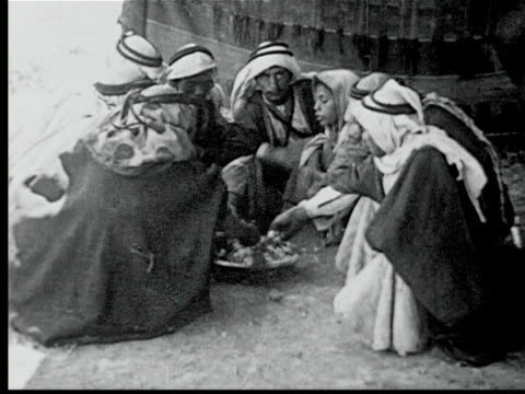 group of bedouins sitting in circle around large dish of food eating w/ hands - anno 1925 video stock e b–roll
